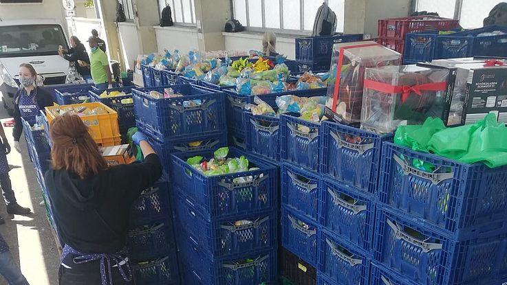 Freiwillige sortiert Lebensmittel aus großen, gestapelten Kisten aus