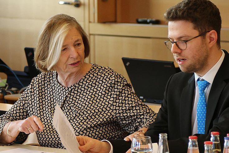 Vorsitzende legt Maximilan Rückert zurückhaltend die Hand auf den Arm, während der einen Text verließt.