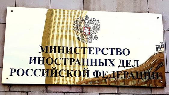 Wertig aussehende Plakette vor der Tür des russischen Aussenministeriums in der sich ein Büroturm spiegelt.