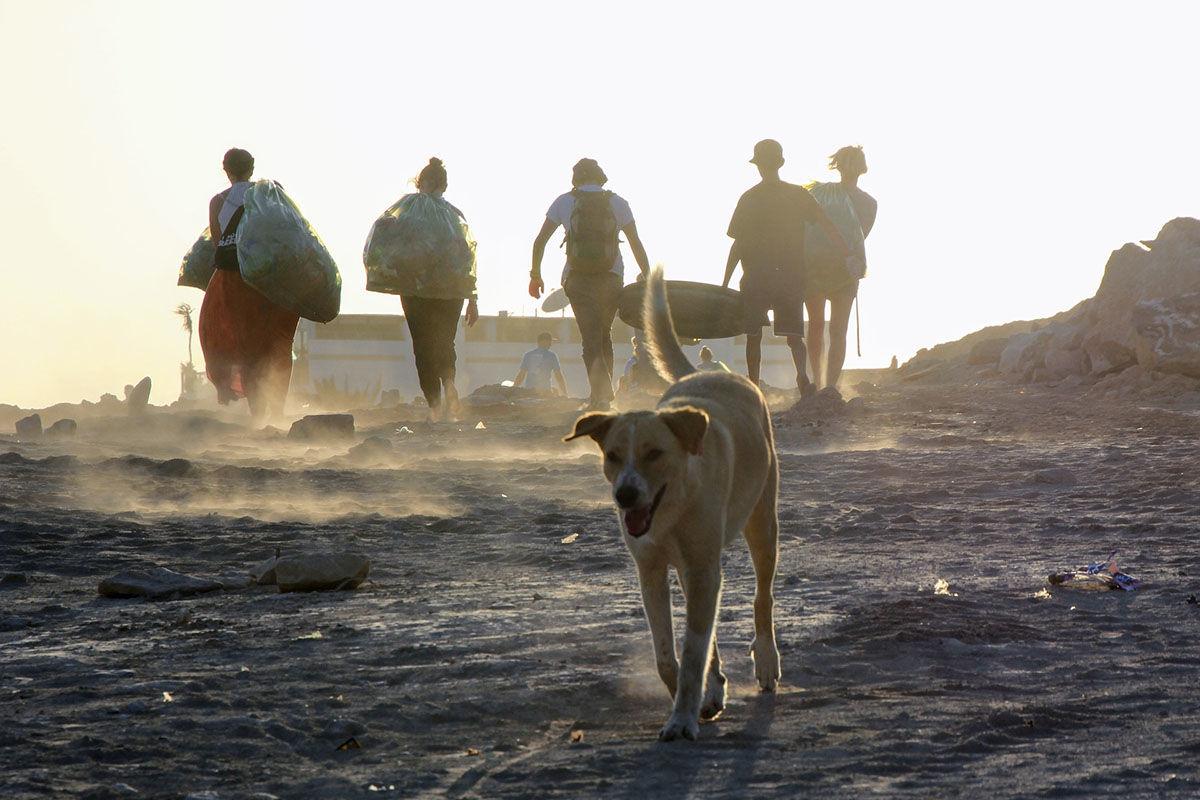 Junge Leute beim Müllsammeln an einem Strand. Große Säcke voller Plastik.
