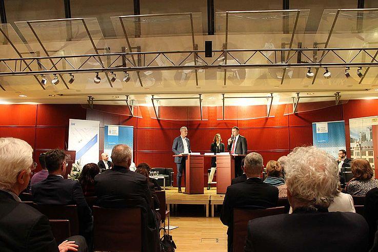 Die drei Personen auf einem Podium zum stehen. Die Pulte einander leicht konfrontativ zugedreht.