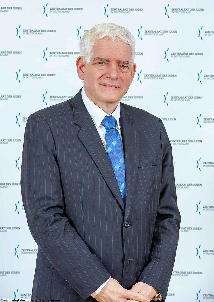 Mann im Anzug vor Stellwand mit dem Logo des Zentralrats der Juden in Deutschland. Ernster Blick.