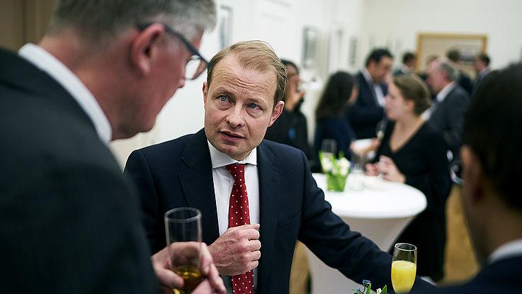 Jüngerer, energetischer Mann mit distinguiertem Gesicht und offensiver Krawatte diskutiert mit einem Konferenzteilnehmer.