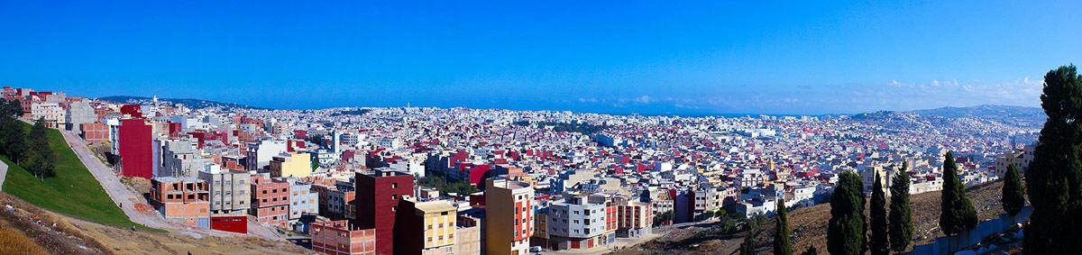 Die Stadt Tanger, flache, niedrige Gebäude unter einem wolkenlosen Himmel. Im Hintergrund lässt sich das Meer erahnen.