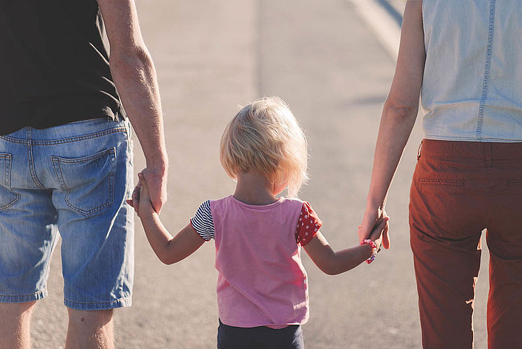 """Eltern mit Kind in der Mitte. """"Engelchen flieg!"""""""