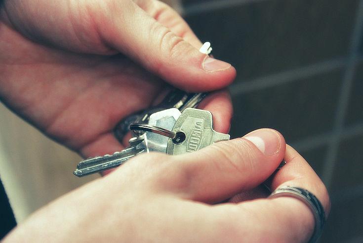 Ein Schlüsselbund in zwei suchenden Händen