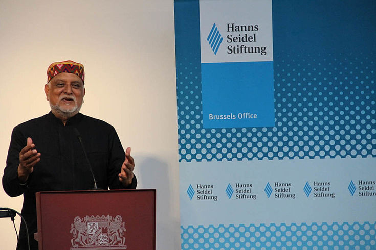 Mangalwadi, älterer Herr mit Bart und orientalisch anm am Rednerpult. Im Hintergrund HSS-Stellwand mit Logo, etc.