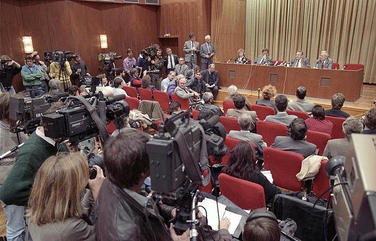 Günther Schabowski leitet eine Pressekonferenz. Im Raum sind Medienvetreter mit Kameras und Fotografen anwesend. Auf dem Podium Vertreter der SED.