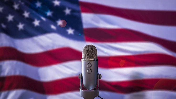 Die amerikanische Flagge weht hinter einem einsamen Mikrofon.