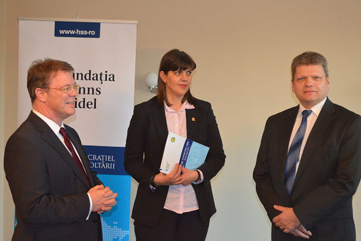 Oliver Groß, Laura Kövesi und Daniel Seiberling im Gespräch vor einem Plakat des rumänischen Büros der HSS