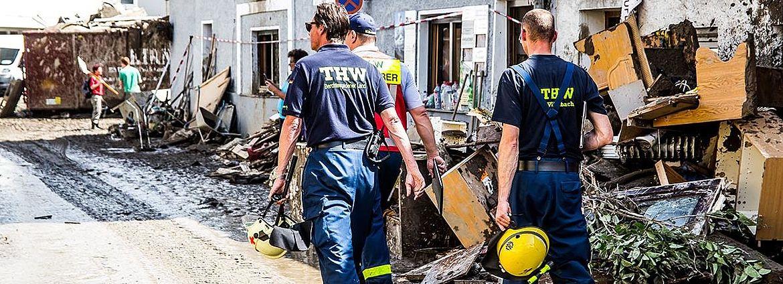 Drei Männer mit Arbeitskleidung des Technischen Hilfswerks räumen in der Verwüstung nach einem Hochwasser auf