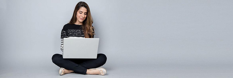 Frau sitzt in bequemen Klamotten auf dem Zimmerboden an der Wand und surft entspannt lächelnd auf ihrem Laptop im Netz (Themenbild)