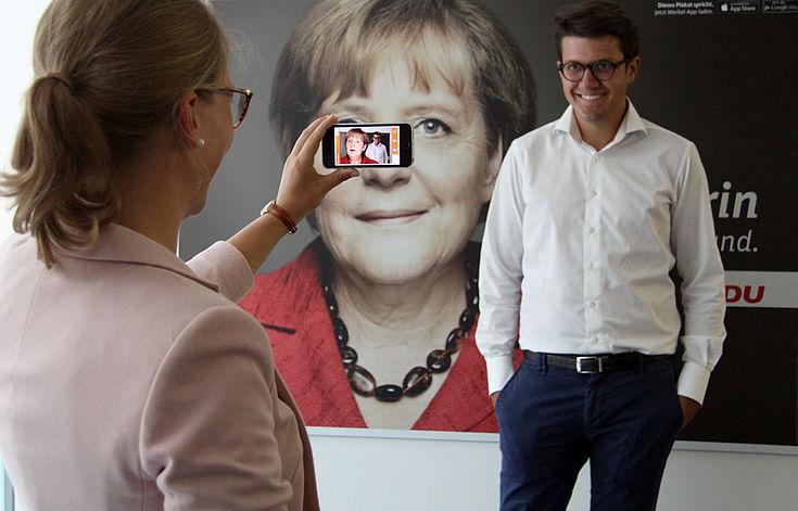 Foto vor einem Wahlplakat der Bundestagswahl 2013