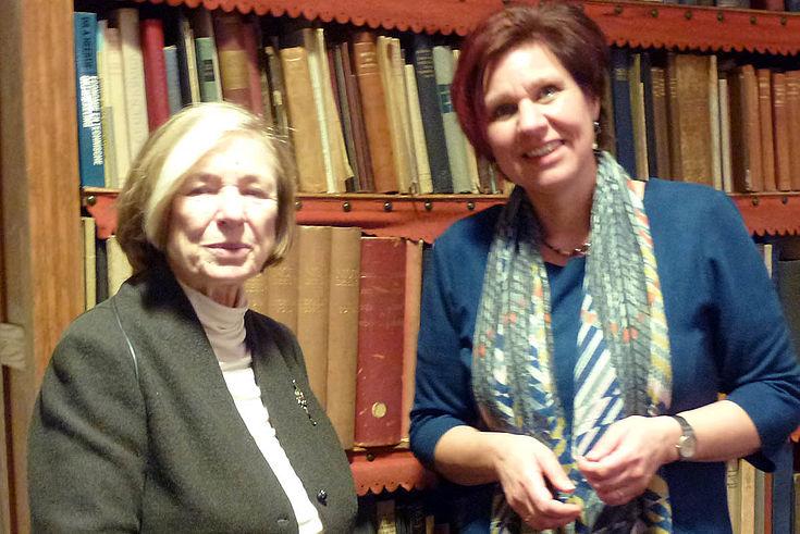 Eine ältere Dame links (Ursula Männle) mit einer elegant gekleideten Ruth Peetoom vor einem Bücherregal.