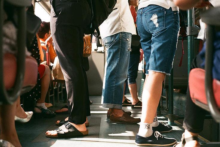 Beine in unerschiedlichen Hosen stehen in einem Straßenbahnabteil. Es scheint sehr voll zu sein.