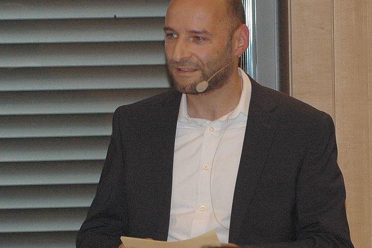 Jüngerer Mann mit Karteikarten und Micro, sricht, weißes Hemd, blaues Sakoo, keine Kravatte