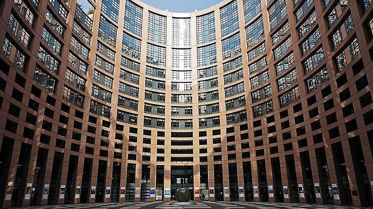 Das Parlament in Brüssel von außen. Viele Fenster, die in einen ovalen Innenhof blicken.