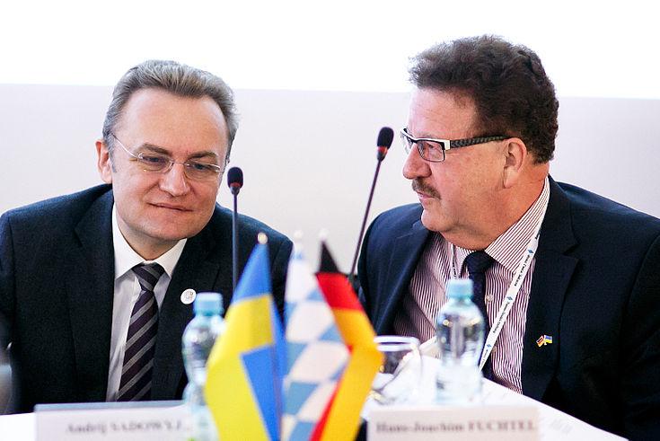 Andreij Sadowij und Hans-Joachim Fuchtel sitzen an einem Konferenztischchen und diskutieren miteinander.