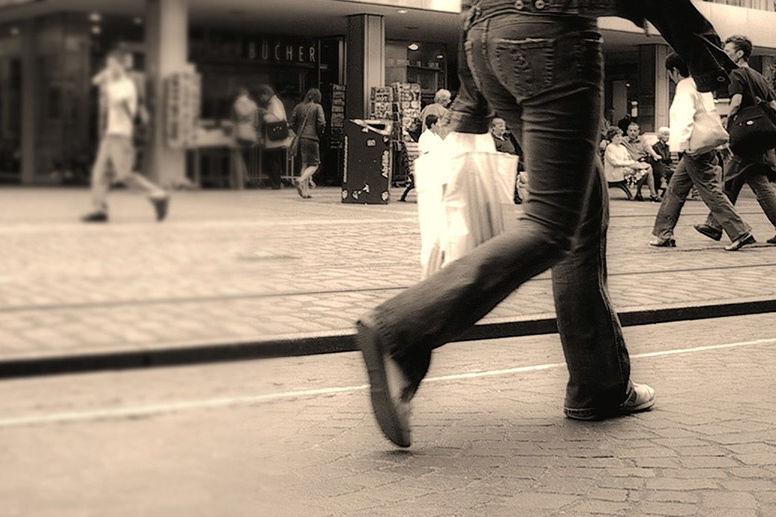 Ein Mensch mit Plastiktüte beim Einkaufen in einer Fußgängerzone
