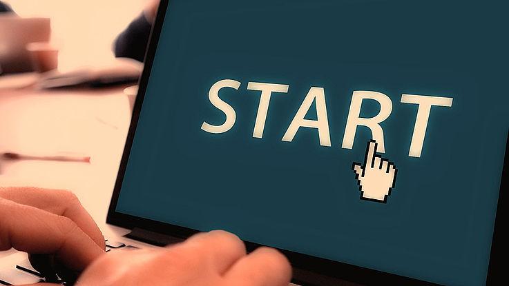 """Themenbild: Zwei Hände auf einer Tastatur. Auf dem Bildschirm das Wort """"START"""""""