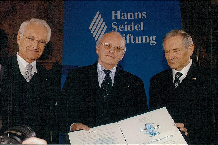 drei ältere Männer in dunklem Anzug vor Logo der Hanns-Seidel-Stiftung