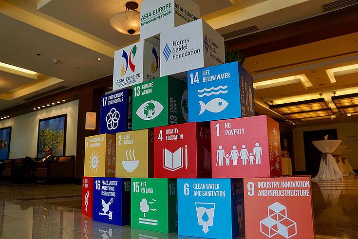Die Nachhaltigkeitsziele sind auf Würfeln gedruckt und als Pyramide aufgestellt. Die oberen drei Würfel sind mit den gastgebenden Organisationen bedruckt.