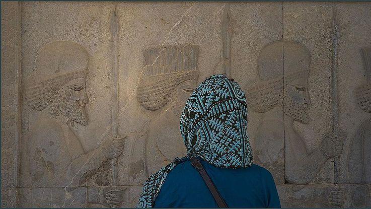 Eine iranische Frau, verscheiert, von hinten aufgenommen, steht vor einer antiken Mauer, auf der persische Krieger mit Speeren in Reih und Glied marschieren.