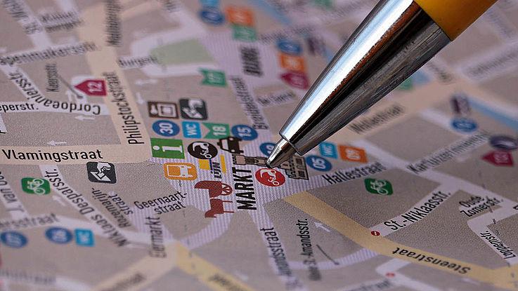 Die Spitze eines Stiftes, die auf einem auf einer Straßenkarte eingezeichneten Marktplatz in der Mitte einer Stadt ruht.