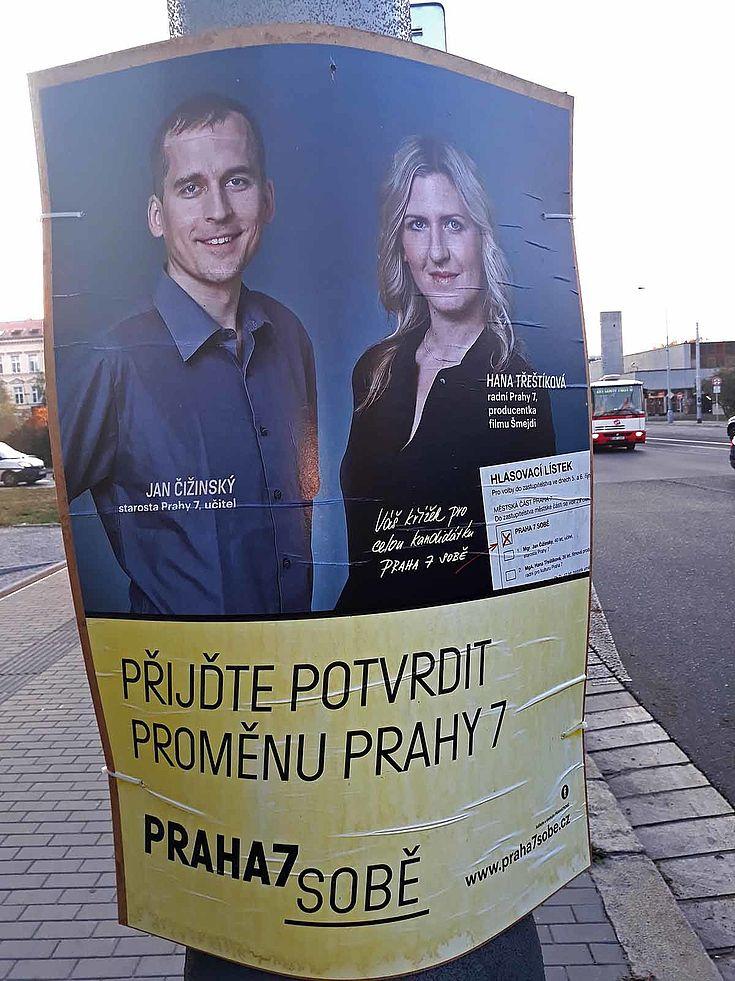 Wahlplakat mit einem lächelnden Mann und einer lächelnden Frau.