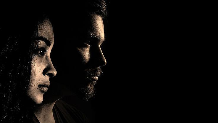 Zwei ernst schauende Menschen, ein Mann, eine Frau, blicken von links nach rechts aus dem Bild.