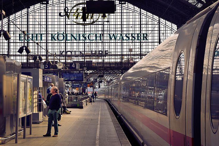 Der Bahnhof Köln. Am Gleis steht ein Mann und studiert den Fahrplan. Hinter ihm hält ein ICE, die Türen geöffnet.
