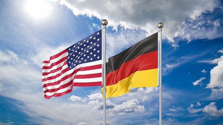 Die beiden Flaggen der USA und Deutschlands wehen nebeneinander im Wind