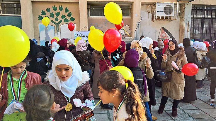 Pauenhofgewimmel der Schüler mit (wohl zur Gelegenheit angeschafften) bunten Luftballons