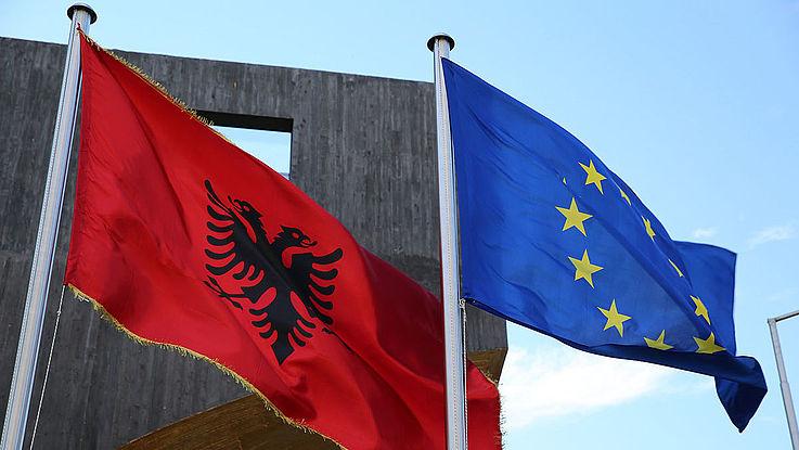 Die Flaggen Albaniens und der EU wehen nebeneinander im Wind.