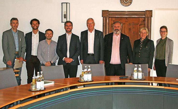 Gruppenbild von Menschen hinter Konferenztisch