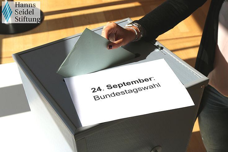 Wahlurne auf Schultisch. Hand wirft gefalteten Wahlzettel in Schlitz.