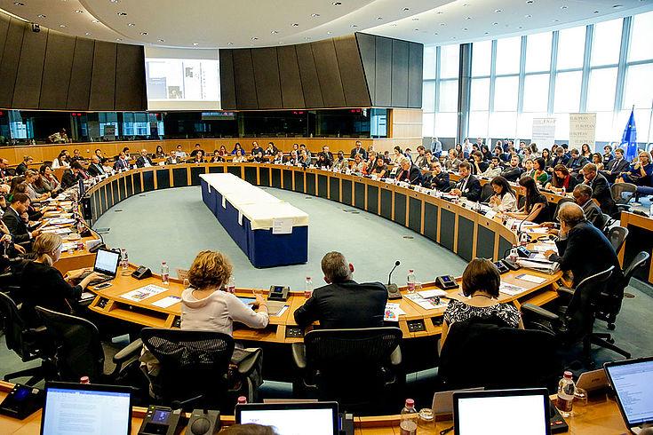 Das Plenum der Konferenz an einem großen runden Tisch mit weiteren Teilnehmern