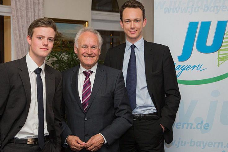 Erwin Huber lächelt jovial zwischen zwei smart gekleideten jungen JU-lern vor einer JU-Stellwand.