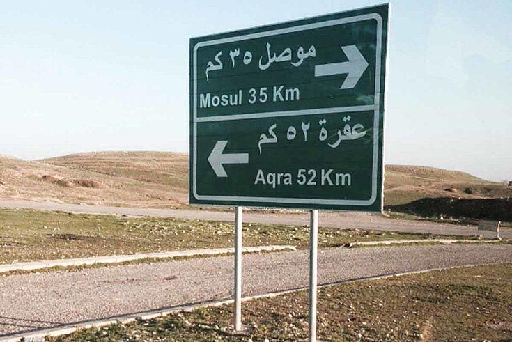 Straßenschild in der Wüste. Nach Mossul rechts, 31 KM. Nach Aqra, links, 52 Km.