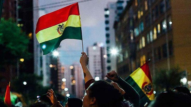 Eine Straße in Boliviens Hauptstadt La Paz, Menschenmengen sind zu sehen, jemand schwenkt eine große Landesfahne