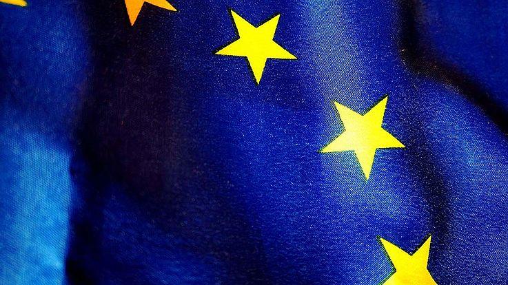 Nahaufnahme der EU-Flagge mit einigen Sternen und dem gewellten Stoff auf den sie gedruckt sind