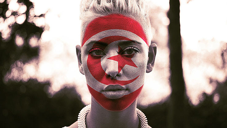 Das mit einer tunesischen Flagge bemahlte Gesicht einer jungen Tunesierin.