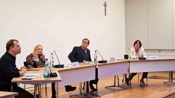 Konferenzraum, in dem die vier Personen an einer langen, gebogenen Tafel sitzen und reden