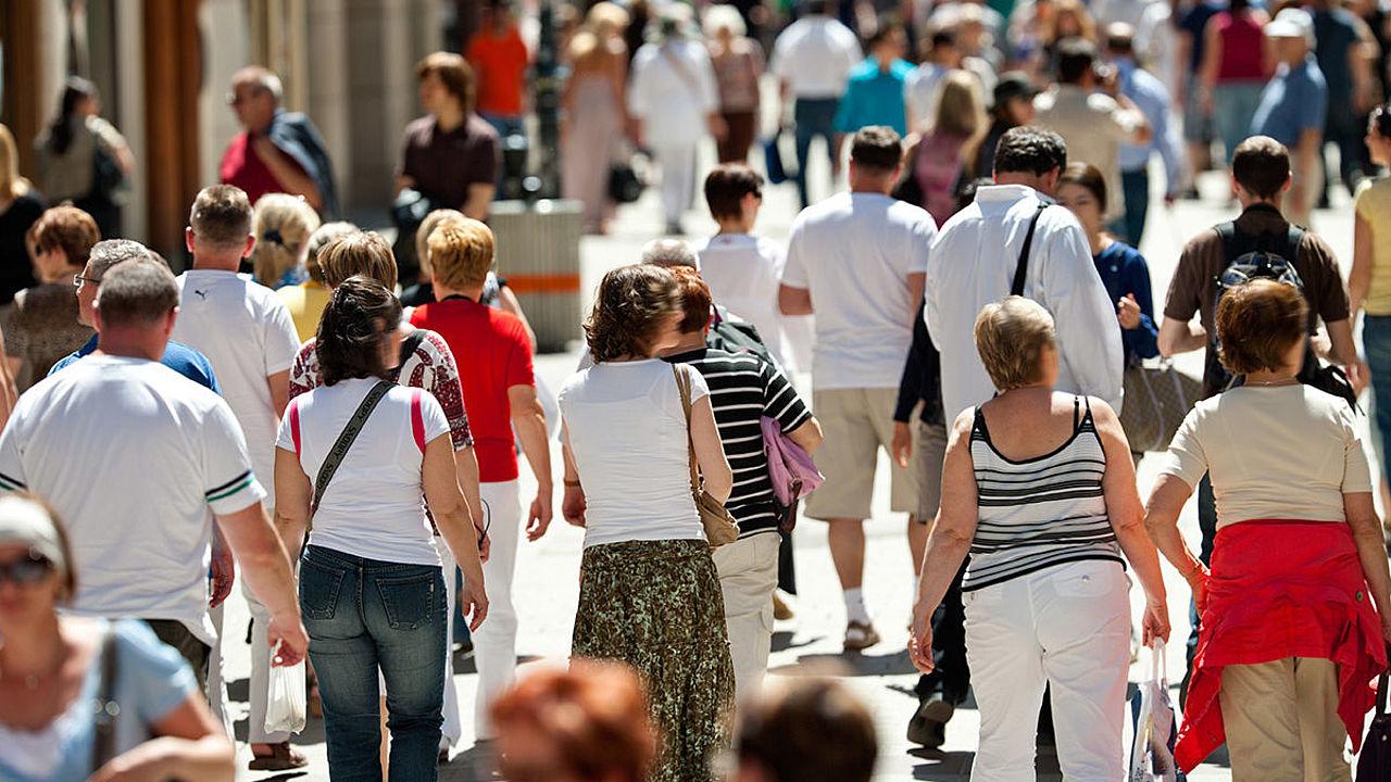 Menschen gehen eine Einkaufstraße entlang