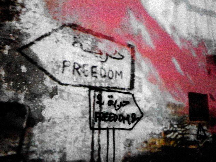 """Grafitto eines Wegweisers der in zwei verschiedene Richtungen zeigt. Darauf ist mit arabischen und römischen Buchstaben """"Freedom"""" geschrieben."""