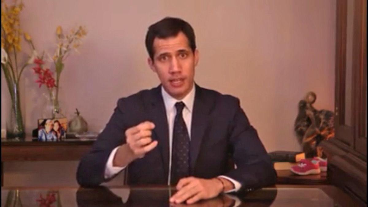 Guaidó an einem Schreibtisch, staatstragend, spricht in die Kamera. Konzentriert.
