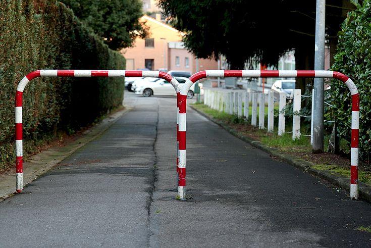 Ein Weg ist durch Metallabsperrungen für Fahrzeuge gesperrt.