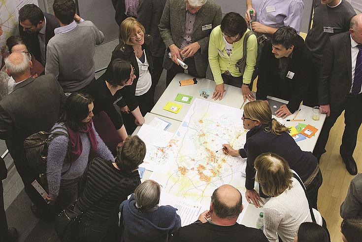 Um einen Tisch mit Kartenmaterial steht ein Gruppe von Menschen und diskutiert mit Gesten in Richtung der Pläne.