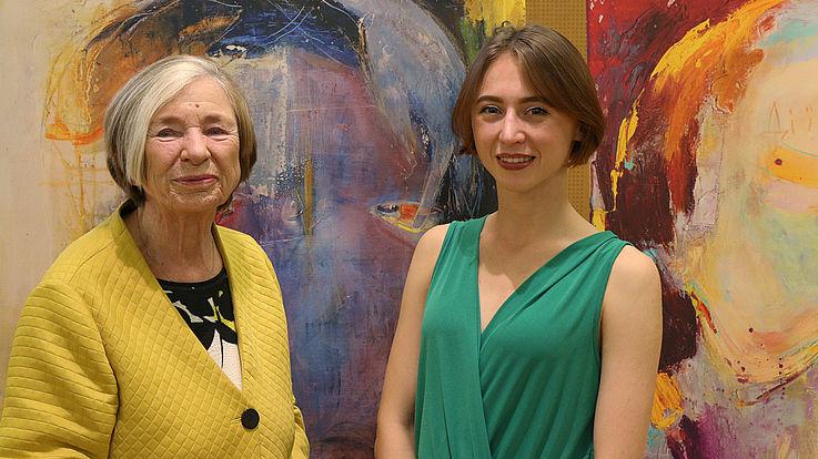"""Zirka Savka mit unserer Vorsitzenden, Prof. Ursula Männle. Für ihre beiden Werke """"Apathy"""" (links) und """"Empathy"""" (rechts) wird gerade nach einem angemessenen, permanenten Platz an den Wänden der Stiftungszentrale gefahndet."""