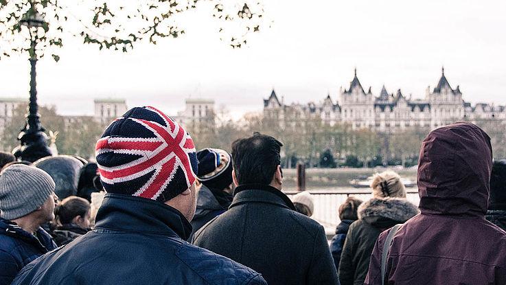 Eine Menge dick angezogener Menschen im wolkenverhangenen London an der Themse gegenüber des Parlametgebäudes. Alle sind vom Betrachter abgewandt. Der vorderste trägt eine Mütze mit dem Union Jack.